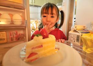 冷蔵庫のケーキをつまみ食いする女の子の写真素材 [FYI01564708]