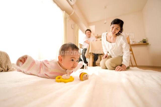 うつぶせの赤ちゃんと両親の写真素材 [FYI01564996]