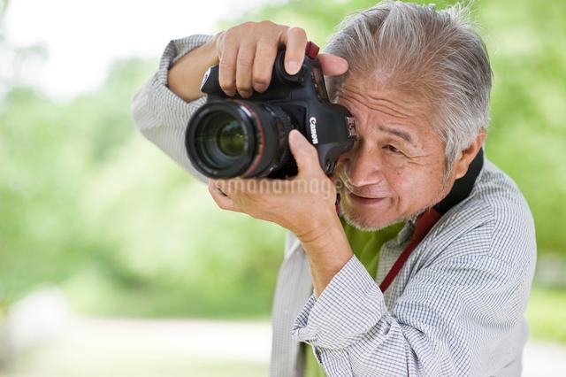 一眼レフカメラを構えるシニア男性の写真素材 [FYI01565018]