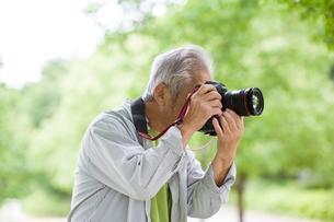 一眼レフカメラを構えるシニア男性の写真素材 [FYI01565039]