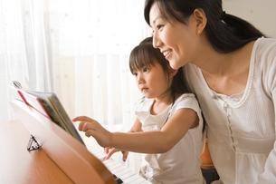 ピアノを弾く女の子とママの写真素材 [FYI01565228]