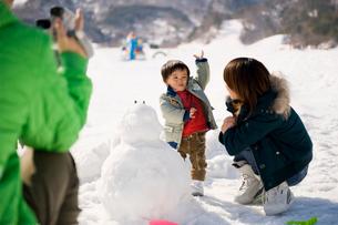 スキー場で遊ぶ母子とビデオ撮影をする父親の写真素材 [FYI01565243]