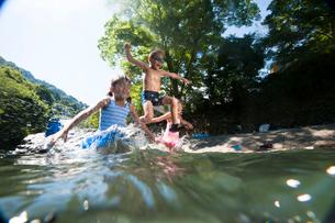 川に飛び込んで遊ぶ子どもたちの写真素材 [FYI01565321]