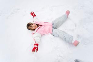 雪の上に寝転ぶ女の子の写真素材 [FYI01565334]