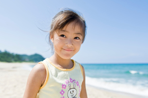 砂浜で微笑む女の子の写真素材 [FYI01565388]