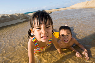 海岸で水遊びをする男の子と女の子の写真素材 [FYI01565478]