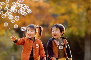 シャボン玉に喜ぶ子供たちの写真素材 [FYI01565503]