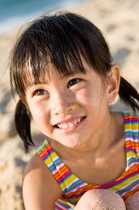 砂浜にいる笑顔の女の子の写真素材 [FYI01565505]