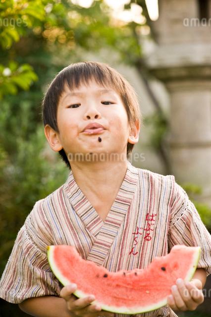 スイカの種を飛ばす男の子の写真素材 [FYI01565523]