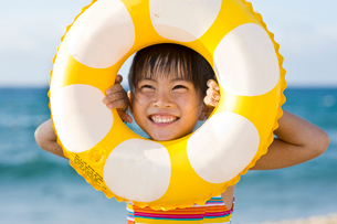 浮き輪から顔をのぞかせる女の子の写真素材 [FYI01565535]