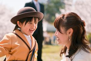 桜の前に立つ入園の男の子と家族の写真素材 [FYI01565697]