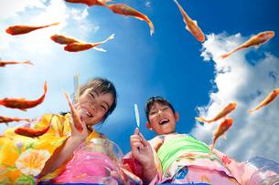 金魚すくいをする浴衣姿の女の子の写真素材 [FYI01565820]