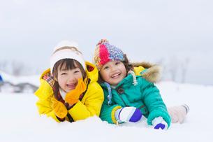 雪の上に寝転ぶ女の子と男の子の写真素材 [FYI01565959]