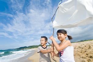 砂浜で白旗を持つ女の子と男の子の写真素材 [FYI01566145]