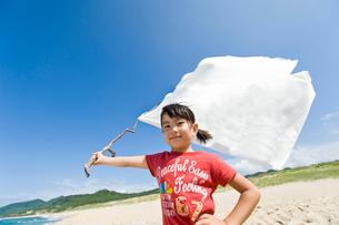 砂浜で白旗を持つ女の子の写真素材 [FYI01566161]