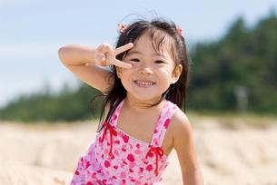 海で遊ぶピースサインの少女の写真素材 [FYI01566186]