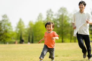 公園で走る父子の写真素材 [FYI01566462]