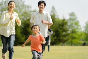 公園で走る親子の写真素材 [FYI01566511]