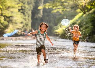 川で網を持って走る子どもの写真素材 [FYI01566565]