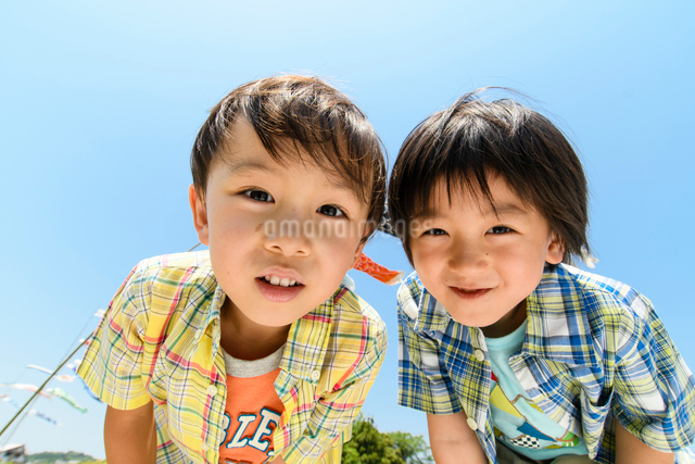 青空の下で覗き込む男の子の写真素材 [FYI01566606]