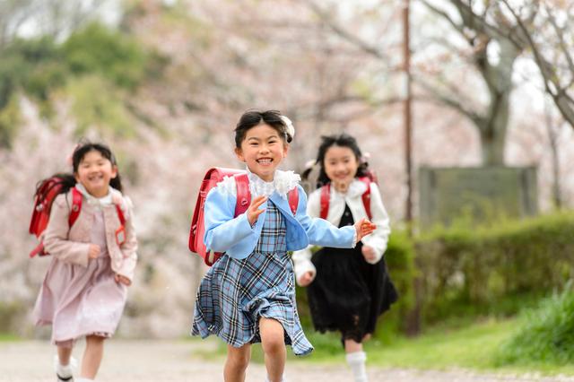 ランドセルを背負ってかけっこする女の子の写真素材 [FYI01566717]
