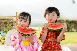 スイカを食べる甚平を着た男の子と浴衣の女の子の写真素材 [FYI01566838]