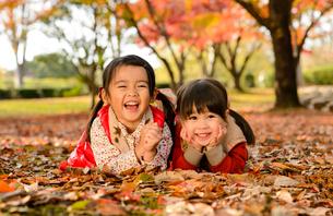 紅葉した落ち葉の上に寝転がる女の子の写真素材 [FYI01566938]