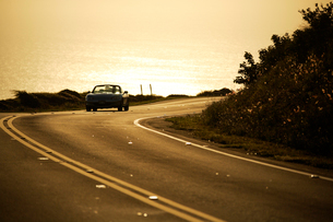 コハラコーストの夕暮れ金色に輝く海とスポーツカーの写真素材 [FYI01566948]