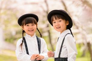 桜の木の前に立つ女の子と男の子の写真素材 [FYI01566973]
