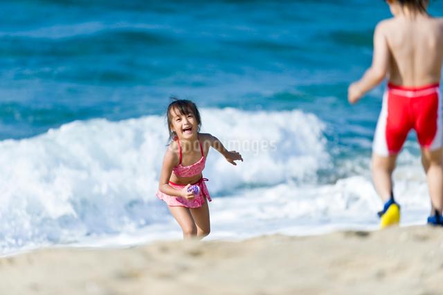 波打ち際で遊ぶ男の子と女の子の写真素材 [FYI01566982]