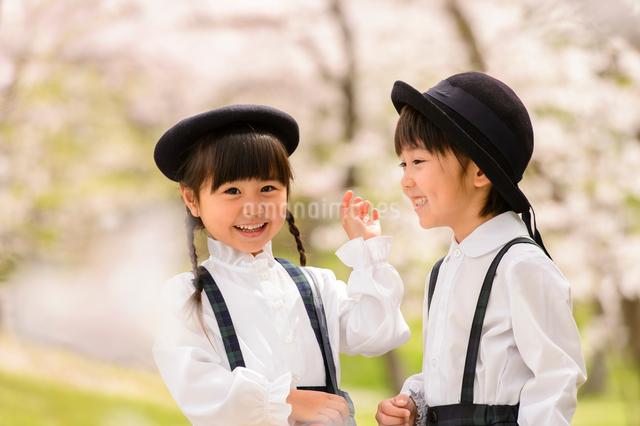 桜の木の前に立つ女の子と男の子の写真素材 [FYI01567036]