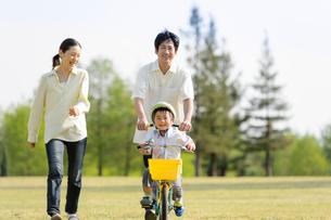 公園で自転車に乗る男の子と一緒に歩く父親と母親の写真素材 [FYI01567039]
