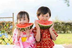 スイカを食べる甚平を着た男の子と浴衣の女の子の写真素材 [FYI01567057]