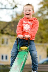 公園のシーソーで遊ぶ男の子の写真素材 [FYI01567083]