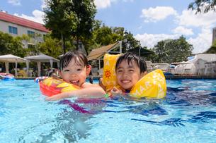 プールで浮き輪で遊ぶ男の子と女の子の写真素材 [FYI01567110]