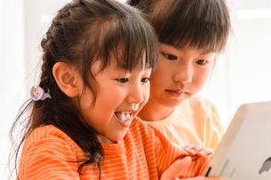 子供部屋でタブレットで遊ぶ女の子の写真素材 [FYI01567201]
