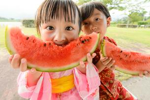 スイカを食べる甚平を着た男の子と浴衣の女の子の写真素材 [FYI01567319]