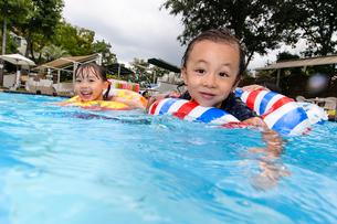 プールで浮き輪で遊ぶ女の子と男の子の写真素材 [FYI01567330]