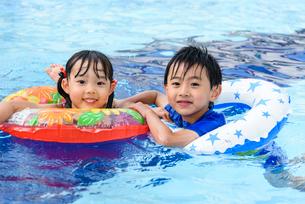 プールで浮き輪で遊ぶ女の子と男の子の写真素材 [FYI01567331]