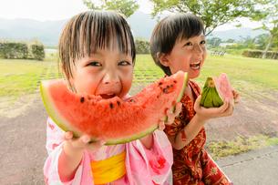 スイカを食べる甚平を着た男の子と浴衣の女の子の写真素材 [FYI01567364]