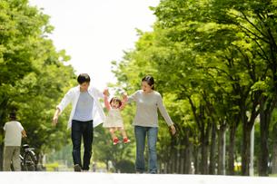 公園で赤ちゃんと手を繋いで歩く家族の写真素材 [FYI01567365]