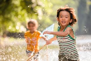 川で網を持って走る子どもの写真素材 [FYI01567510]