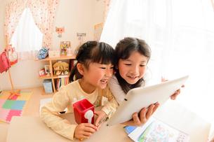 子供部屋でタブレットで遊ぶ女の子の写真素材 [FYI01567528]