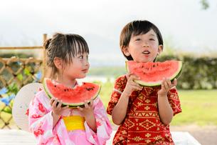 スイカを食べる甚平を着た男の子と浴衣の女の子の写真素材 [FYI01567581]