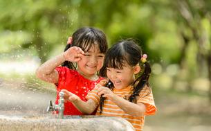 公園の水飲み場で水遊びする女の子の写真素材 [FYI01567582]