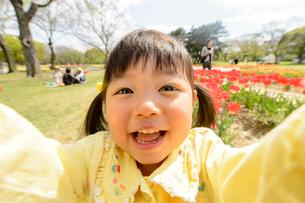 春の公園でチューリップ畑で遊ぶ女の子の写真素材 [FYI01567604]