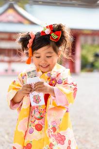 お年玉袋の中を見る晴れ着を着た女の子の写真素材 [FYI01567665]