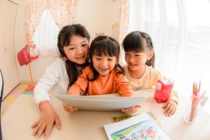 子供部屋でタブレットで遊ぶ女の子の写真素材 [FYI01567670]