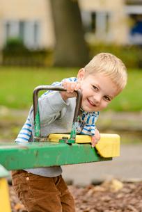 公園のシーソーで遊ぶ男の子の写真素材 [FYI01567674]