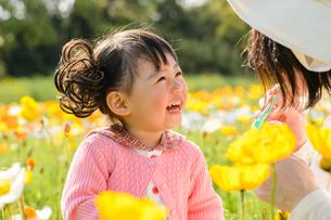 ポピー咲く花畑でシャボン玉で遊ぶ女の子とお母さんの写真素材 [FYI01567682]